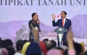 Presiden Jokowi berdialog dengan seorang warga pada penyerahan 15.000 sertifikat, di halaman parkir Sirkuit Internasional Sentul, Babakan Madang, Kabupaten Bogor, Jawa Barat, Selasa (6/3). (Foto: JAY/Humas)