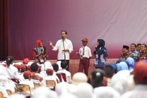 Presiden Jokowi saat menyerahkan bantuan sosial di GOR Tri Dharma PT Petrokimia Gresik, Kabupaten Gresik, Provinsi Jawa Timur, Kamis (8/3). (Foto: Humas/Oji).