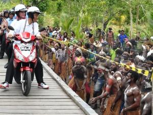 Presiden Jokowi memboncengi Ibu Negara Iriana saat melakukan kunjungan kerja di Kabupaten Asmat, Kamis (12/4). (Foto: BPMI)