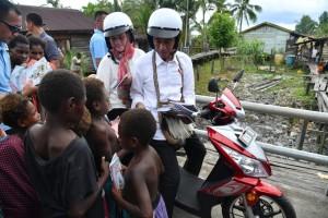 Presiden Jokowi dan Ibu Negara Iriana menyapa anak-anak saat kunjungan kerja berkunjung ke Kabupaten Asmat, Kamis (12/4). (Foto: BPMI)