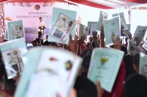 Presiden saat menyerahkan sertifikat di Lapangan Kantor Bupati Jayapura, Rabu (11/4). (Foto: BPMI).