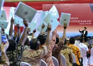 Presiden Jokowi menghitung sertifikat yang ditunjukkan warga saat penyerahan 3.973 sertifikat di GOR Sasana Krida Anoraga, Kabupaten Pasuruan, Jatim, Sabtu (12/5) siang. (Foto: Setpres)