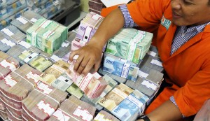 Uang Tunai BNI Petugas mengatur tumpukan uang di cash center BNI, Kamis (29/12). Uang tunai yang disiapkan BNI untuk memenuhi kebutuhan selama masa liburan Natal 2016 dan Tahun Baru 2017 mencapai sekitar Rp 11 triliun. Investor Daily/David Gita Roza