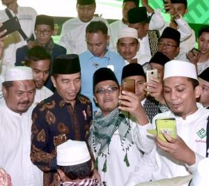 Presiden Jokowi melayani permintaan selfi saat hadir pada Halalbihalal dan Silaturahim dengan Solidaritas Ulama Muda Jokowi (Samawi), di SICC, Bogor, Jabar, Selasa (10/7) malam. (Foto: Setpres)