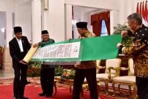 Presiden Jokowi bersama Menteri Agama, Utusan Khusus Presiden Din Syamsudin, dan Tan Sri Li Kim Yew, membentangkan mushaf Al Quran, dalam pembukaan MTQ Internasional, di Istana Negara, Jakarta, Rabu (11/7) sore. (Foto: OJI/Humas)