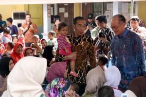 Presiden Jokowi menggendong seorang bocah saat mengajak Presiden Bank Dunia meninjau program penanganan stunting di SDN Tangkil 01, Kecamatan Caringin, Sukabumi, Jabar, Rabu (4/7) siang. (Foto: OJI/Humas)