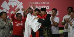 President Jokowi and Chairman of the Indonesian Pencak Silat Association (IPSI) Prabowo Subianto share a group hug with Hanifan Yudani Kusumah after the athlete wins pencak silat final at Pencak Silat Center, Taman Mini Indonesia Indah, Jakarta, Wednesday (29/8)