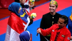 President Jokowi handled over the gold medal to Defia Rosmaniar, taekwondo athlete who won Indonesia's first gold in 2018 Asian Games. (Photo: IST)