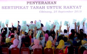 Presiden Jokowi menghitung sertifikat yang diterima warga Bogor, di Lapangan Stadion Pakansari. Bogor, Jabar, Selasa (25/9) pagi. (Foto: Rahmat/Humas)