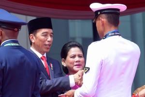 Presiden Jokowi didampingi Ibu Negara Iriana menyerahkan potongan tumpeng kepada salah satu prajurit TNI, usai upacara HUT ke-73 TNI, di Plaza Mabes TNI, Cilangkap, Jakarta, Jumat (5/10) pagi. (Foto: OJI/Humas)