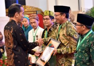 Presiden Jokowi menyerahkan sertifikat hak tanah kepada kelompok masyarakat, di Istana Negara, Jakarta, bulan September lalu. (Foto: Dok. Humas Setkab)