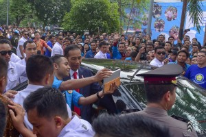 President Jokowi taking a picture with a student after giving scientific oration at 65th Dies Natalis UKI, in Cawang, Jakarta, Monday (15/10). (Photo: JAY/PR)