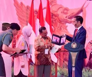 Presiden Jokowi menyerahkan foto kepada warga saat menghadiri penyerahan 5.083 sertifikat, di GOR Segiri, Samarinda, Kaltim, Kamis (25/10) siang. (Foto: BPMI Setpres)