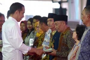 Presiden Jokowi menyerahkan sertifikat kepada warga di wilayah Jakarta Utara, di Lapangan C-04 Kawasan Berikat Nusantara, Marunda, Cilincing, Jakarta Utara, Rabu (17/10) sore. (Foto: OJI/Humas)