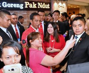 Presiden Jokowi diajak berfoto bersama warga saat makan siang rumah makan khas Indonesia Bebek Goreng Pak Ndut di Lucky Plaza, Orchard Road, Singapura, Selasa (13/11). (Foto: BPMI)