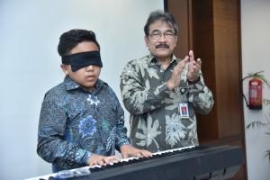 Pemerang rekor dunia mainkan piano dengan mata tertutup, Jefri Setiawan mendemonstrasikan kemampuannya di hadapi Deputi Seskab bidang PMK Surat Indijarso, di Gedung III Kemensetneg, Jakarta, Kamis (1/11) siang. (Foto: AGUNG/Humas)