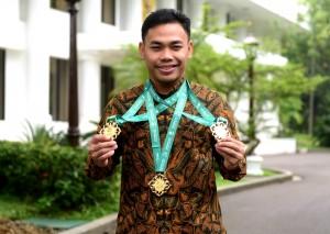 Juara dunia angkat besi kelas 61 kg Eko Yuli Irawa menunjukkan 3 medali emas yang baru diperolehnya, di Istana Merdeka, Jakarta, Kamis (8/11) pagi. (Foto: Rahmat/Humas)