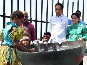Presiden Jokowi dan Ibu Negara Iriana memperhatikan anak-anak yang menyimpan pesan pada Monumen Kapsul Waktu, di Merauke, Provinsi Papua, Jumat, (16/11). (Foto: BPMI)