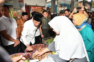 President Jokowi and Governor of East Java Soekarwo check prices at a market in East Java, Monday (19/11). Photo by: BPMI