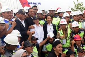 Presiden Jokowi didampingi Ibu Negara Iriana dan Menteri BUMN berfoto bersama para pekerja yang menyelesaikan pembangunan jalan tol Trans Jawa, di Jembatan Kali Kuto, Semarang, Jateng, Kamis (20/12). (Foto: OJI/Humas)