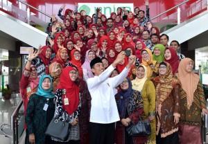 Presiden Jokowi berswafoto saat meninjau Unisa di Dusun Mlangi, Kabupaten Sleman, Kamis (6/12). (Foto: BPMI).