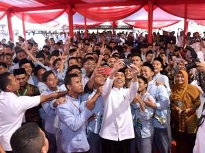 Presiden Jokowi berselfi bersama siswa-siswa saat menghadiri Milad 1 Abad Madrasah Mu'allimin-Mu'allimaat Muhammadiyah, di Yogyakarta, Kamis (6/12) pagi. (Foto: Setpres)