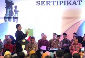 Presiden Jokowi menunjukkan sertifikat saat penyerahan 5000 sertifikat tanah untuk warga Provinsi DKI Jakarta. di Taman Cakung, Jakarta, Senin (3/12) sore. (Foto: Rahmat/Humas)