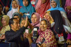 President Jokowi takes a group photo with Family Hope Program recipients at East Jakarta Sports Hall, Jakarta, Monday (3/12). (Photo: AGUNG/PR)
