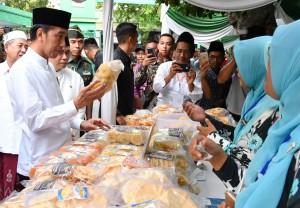 Presiden meninjau stan yang menjual makanan saat peresmian Bank Wakaf MIkro di Pondok Pesantren Mamba'ul Ma'arif Denanyar, Kabupaten Jombang, Jawa Timur, Selasa (18/12). (Foto: BPMI)