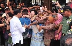 Warga Keluarahan Kalianya, Tambora, Jakarta Barat, berebut untuk bisa bersalaman dengan Presiden Jokowi, yang meninjau pelaksanaan Mekaar di Lapangan Persima. (Foto: JAY/Humas)