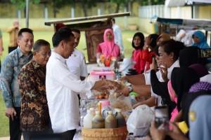 Presiden Jokowi membeli produk peserta program Mekaar, di Stadion Gongseng, Cijantung, Jakarta Timur, Kamis (10/1) sore. (Foto: OJI/Humas)