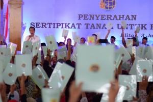 Presiden Jokowi menghitung sertifikat hak atas tanah yang diterima warga di Pendopo Kabupaten Blitar, Jatim, Kamis (3/1) sore. (Foto: OJI/Humas)
