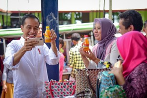 President Jokowi takes a selfie with one of Mekaar beneficiaries' product in Muara Gembong, Bekasi, West Java, Wednesday (30/1). (Photo by: Agung/Public Relations).