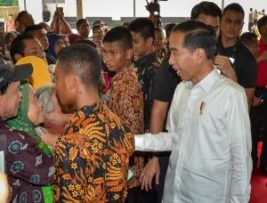 Presiden Jokowi membalas uluran tangan warga yang ingin bersalaman dirinya saat penyerahan 3.000 sertifikat di Lapangan Bola Arcici, Rawasari, Cempaka Putih, Jakpus, Sabtu (26/1) siang. (Foto: AGUNG/Humas)