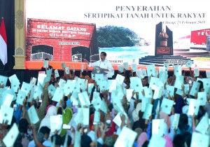 Recipients of land certificates raise their certificates up in the air before President Jokowi, at the distribution of land certificates, in Cilacap, Central Java, Monday (25/2). (Photo by: Rahmat/ PR Division)