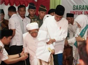 President Jokowi helping K.H. Maimoen Zubir to sit at Sarang's Mass Dzikir for a Developed Indonesia, at Al Anwar Sarang Islamic Boarding School, Rembang, Central Java, Friday (1/2). (Photo by: Dhinda M/PR Division)