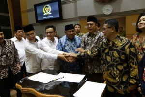 Minister of Religious Affairs and leaders of Commission VII DPR stack hands after the signing of 2019 hajj pilgrimage cost, at Indonesian Parliament Building, Jakarta, Monday (4/2). (Photo: PR of Ministry of Religious Affairs)
