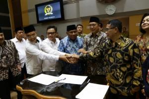 Menag dan pimpinan Komisi VIII DPR saling bertumpuk tangan usai penandatanganan kesepakatan BPIH 1440H/2019M, di Gedung DPR RI, Jakarta, Senin (4/2). (Foto: Humas Kemenag)