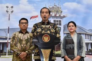 Presiden Jokowi didampingi Ibu Negara Iriana dan KSP Moeldoko menyampaikan keterangan pers sebelum bertolak ke Singapura, di Lanud Halim Perdanakusuma, Jakarta, Kamis (21/2) siang. (Foto: OJI/Humas)