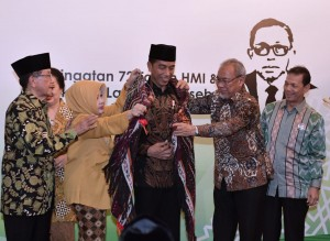 Keluarga pahlawan nasional Lafran Pane disaksikan Akbar Tanjung memasangkan ulos kepada Presiden Jokowi, pada syukuran di Jakarta, Rabu (5/2) malam. (Foto: Setpres)