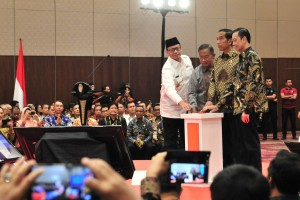 Presiden Jokowi didampingi sejumlah pejabat menekan tombol tanda dimulainya pembukaan Rakornas Investasi, di Nusantara Hall ICE BSD, Kabupaten Tangerang, Selasa (12/3) pagi. (Foto: JAY/Humas)