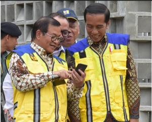residen Jokowi tersenyum melihat handphone yang ditunjukkan Seskab pada acara PeluncuranSertifikasi Tenaga Kerja Konstruksi Indonesia di Istora GBK, Senayan, Jakarta, Selasa (12/3) siang. (Foto: OJI/Humas)