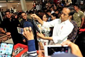 Presiden Jokowi menawar seekor ikan usai peresmian PIM Muara Baru, di Koja, Jakarta Utara, Rabu (13/3) malam. (Foto: JAY/Humas)
