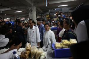 Presiden Jokowi dan Ibu Negara Iriana tersenyum menyapa warga saat meninjau Pasar Badung, di Denpasar, Bali, diresmikannya Jumat (22/3) petang. (Foto: OJI/Humas)