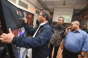 Minister of Communication and Informatics Rudiantara signs an exhibition poster at the 2018 Kilas Balik photo exhibition and book launch in Antara Photo Journalism Gallery, Jakarta, Friday (26/4).