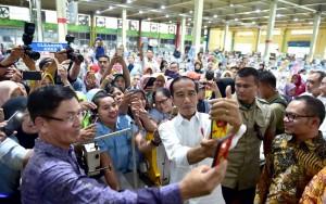 Presiden Jokowi melayani permintaan foto para buruh saat berkunjung ke pabrik sepatu PT KMK Global Spors, di Kel. Talagasari, Kec. Cikupa, Kabupaten Tangerang, Banten, Selasa (30/4) siang. (Foto: Setpres)