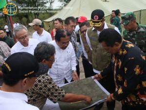 Menteri ATR/Kepala BPN Sofyan Jalil memperhatikan peta penggunaan tanah telantar untuk relokasi korba gempa di Palu, Sulteng, Jumat (19/4). (Foto: Humas Kementerian ATR/BPN)