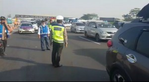 Officers monitor the implementation of One-way system at Cikampek tollgate, West Java, Thursday (30/5). (Photo by: Info Mudik 2019)