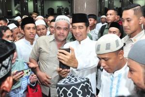 Presiden Jokowi melayani permintaan foto warga usai melaksanakan salat tarawih di Masjid Darul Arqam, Palangka Raya, Kalteng, Selasa (7/5) malam. (Foto: JAY/Humas)