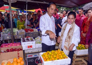 President Jokowi and First Lady Ibu Iriana purchase some oranges during a visit to Sukawati Traditional Market, Gianyar Regency, Bali, Friday (14/6). (Photo by: Agung/PR)